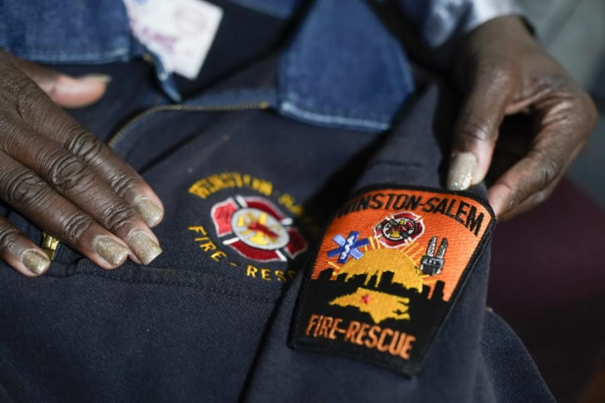 Timika Ingram holds a jacket she had when she was a firefighter on Thursday, Nov. 19, 2020, in Charlotte, N.C. A group of Black firefighters in a North Carolina city have filed a grievance over conditions they have endured for more than 30 years.