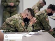 Minnesota National Guard chaplains bow during a prayer after a time of devotion Oct. 19, 2020 in St. Paul, Minn. The role of faith leaders who serve as National Guard chaplains has grown more crucial, and more challenging, as thousands of soldiers and airmen, most of them in their 20s, have been increasingly deployed not only in long-lasting overseas wars but in civil unrest across a deeply polarized United States, including the civil unrest following the death of George Floyd at the hands of Minneapolis police.