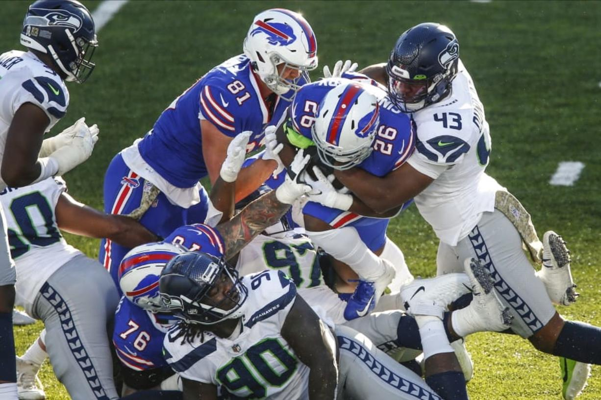 Seattle's Carlos Dunlap (43) tackles Buffalo's Devin Singletary (26) .