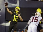 Oregon's Tyler Shough, left, throws downfield against Stanford during the second quarter of an NCAA college football game Saturday, Nov. 7, 2020, in Eugene, Ore.