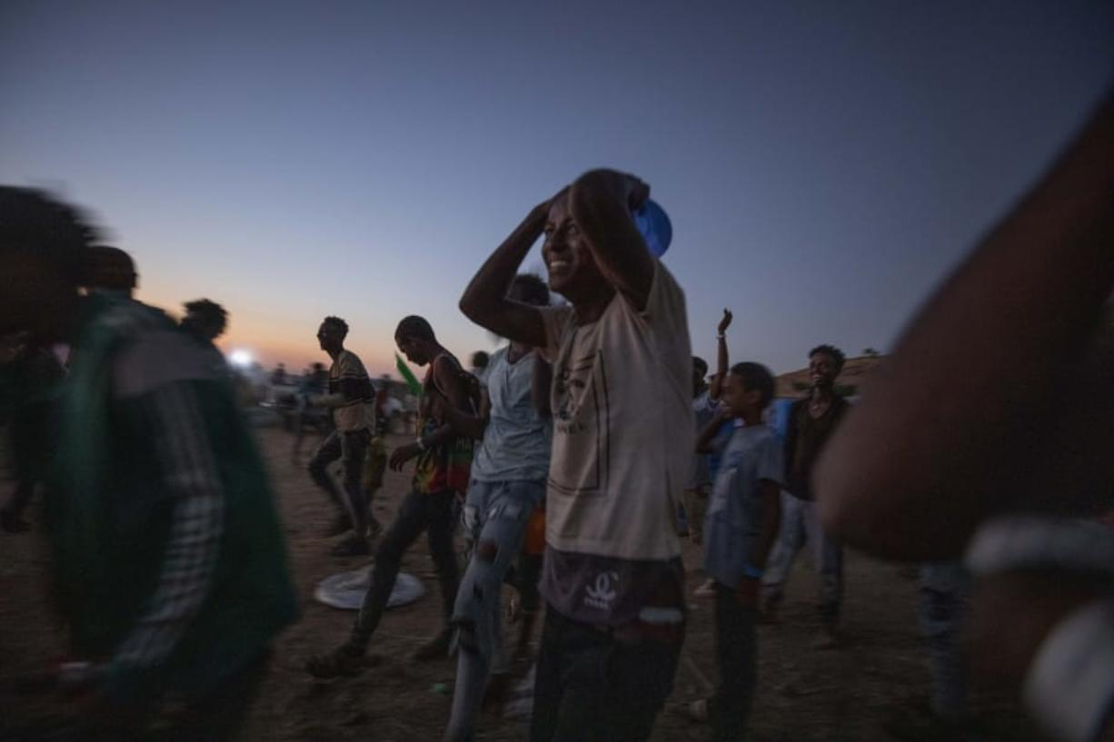 "Tigray men who fled the conflict in Ethiopia's Tigray region, run to recieve cooked rice from charity organization Muslim Aid, at Umm Rakouba refugee camp in Qadarif, eastern Sudan, Friday, Nov. 27, 2020. Ethiopian Prime Minister Abiy Ahmed again ruled out dialogue with the leaders of the defiant Tigray region Friday but said he was willing to speak to representatives ""operating legally"" there during a meeting with three African Union special envoys trying to end the deadly conflict between federal troops and the region's forces."
