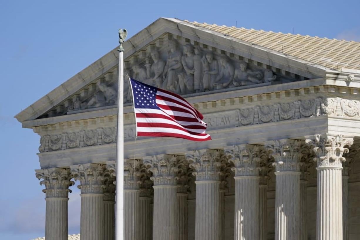 FILE - In this Nov. 2, 2020, file photo an American flag waves in front of the Supreme Court building on Capitol Hill in Washington. The Supreme Court is hearing arguments over whether the Trump administration can exclude people in the country illegally from the count used for divvying up congressional seats.