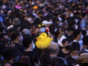 Inflatable yellow ducks, which have become a good-humored symbol of resistance during anti-government rallies, are held by a protester during a rally Wednesday, Nov. 25, 2020 in Bangkok, Thailand. Pro-democracy demonstrators in Thailand on Wednesday again took to the streets of the capital, even as the government escalated its legal battle against them, reviving the use of a harsh law against defaming the monarchy.