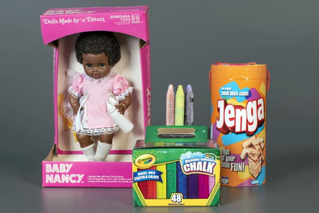 This photo, provided by the National Toy Hall of Fame, shows Baby Nancy, by Shindana Toys; Sidewalk Chalk, by Crayola; and Jenga, by Parker Brothers, left to right, that were inducted into the National Toy Hall of Fame on Thursday, Nov, 5, 2020. The honorees were chosen by a panel of experts from among 12 finalists and will be on permanent display inside The Strong National Museum of Play, in Rochester, New York.
