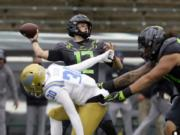 Oregon's Tyler Shough throws down field under pressure from UCLA's Elisha Guidry during the second quarter of an NCAA college football game Saturday, Nov. 21, 2020, in Eugene, Ore.