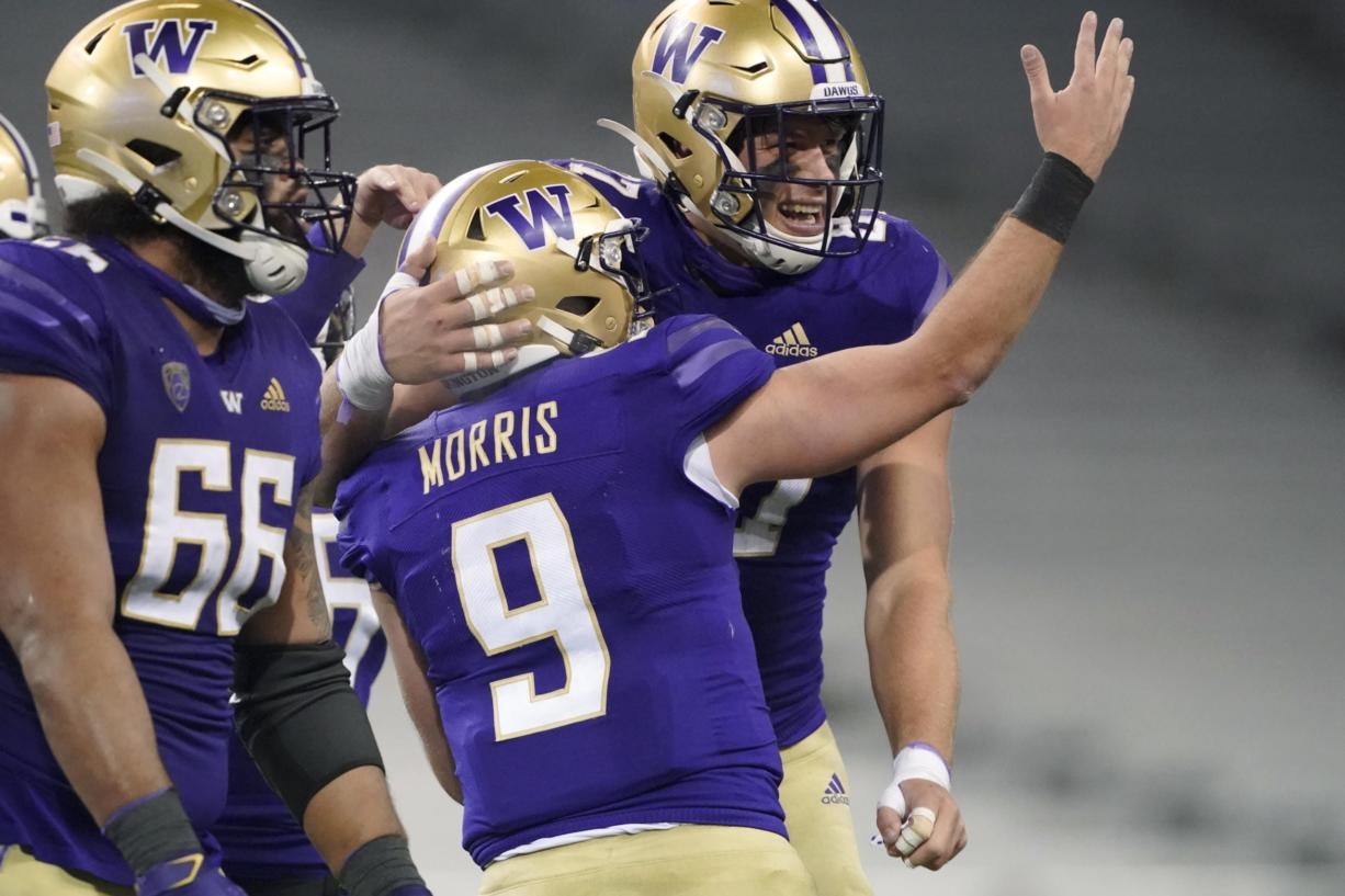 Washington quarterback Dylan Morris (9) celebrates with tight end Cade Otton, right, after Morris passed to Otton for a touchdown against Utah in the final minute of an NCAA college football game Saturday, Nov. 28, 2020, in Seattle. Washington won 24-21. (AP Photo/Ted S.