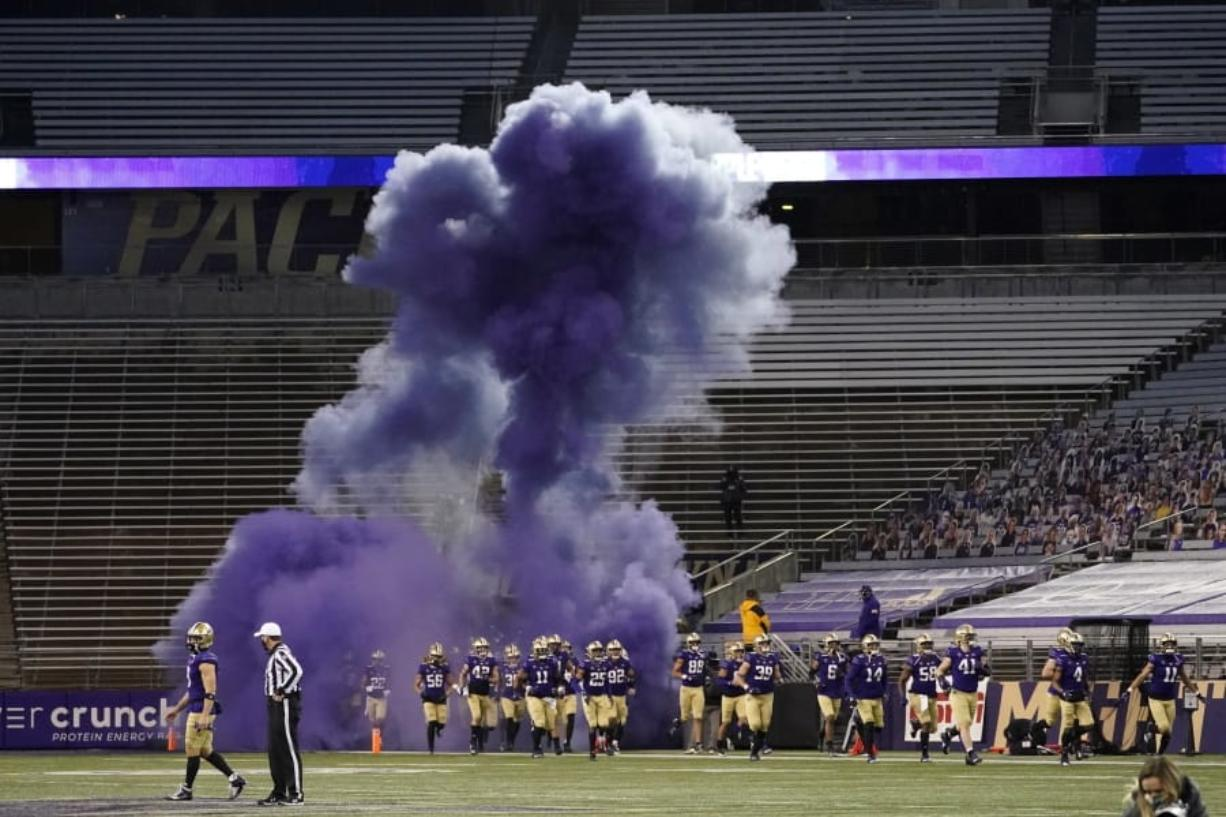 Washington players run out of a tunnel through a cloud of purple smoke in front of empty seats at Husky Stadium before an NCAA college football game against Utah, Saturday, Nov. 28, 2020, in Seattle. Due to the COVID-19 pandemic, no fans were in attendance at the game. (AP Photo/Ted S.
