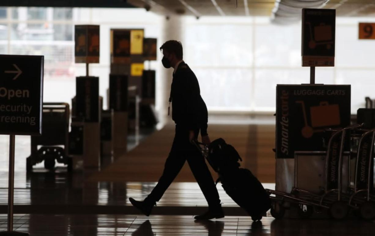 FILE - In this Thursday, April 9, 2020, file photo, a lone airline crew member pulls his bags behind him as he walks through the baggage-claim area at Denver International Airport in Denver, amid the coronavirus outbreak.