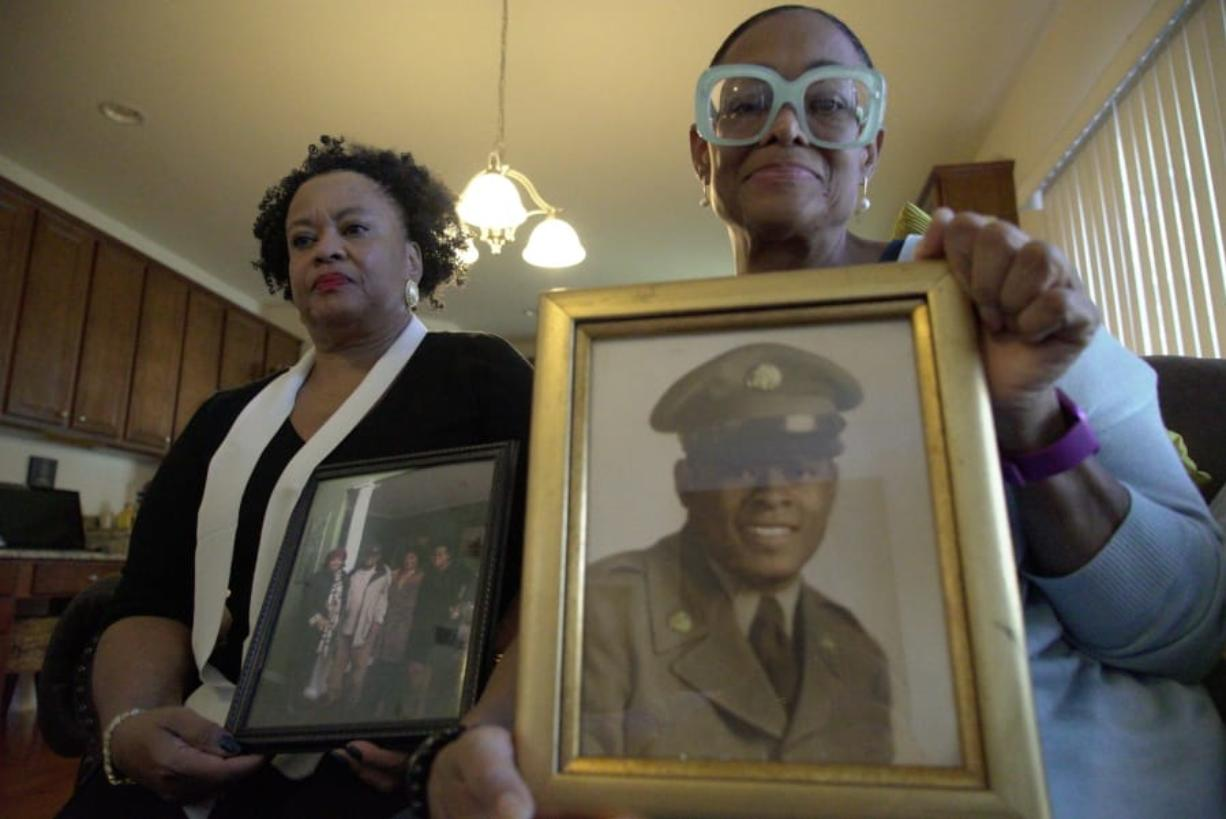 Sisters Barbara Leak-Watkins, right, and Alberta Lynn Fantroy pose with photos of their late father, Alex Leak Jr., at Watkins' home in Greensboro, N.C., on Wednesday, Nov. 4, 2020. The Army veteran died in July after collapsing from dehydration at his assisted-living facility, and the family believes pandemic-related neglect is to blame. As more than 90,000 of America's long-term care residents have died in a coronavirus pandemic that has pushed staffs to the limit, advocates for the elderly say a tandem wave of death separate from the virus has quietly claimed thousands more, often because overburdened workers haven't been able to give them the care they need. (AP Photo/Allen G.