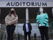 """Jim Howard, a drama teacher at Westwood, Mass., High School, center, stands with his student actors outside the school's auditorium after working on their virtual performance of Shakespeare's """"Romeo and Juliet.""""  From left are Ryan Kaplan, who portrays the friar, Lucy Vitali, who portrays Juliet, Howard, Cassidy Hall, who portrays the nurse, and Alex Mansour, who portrays Romeo."""