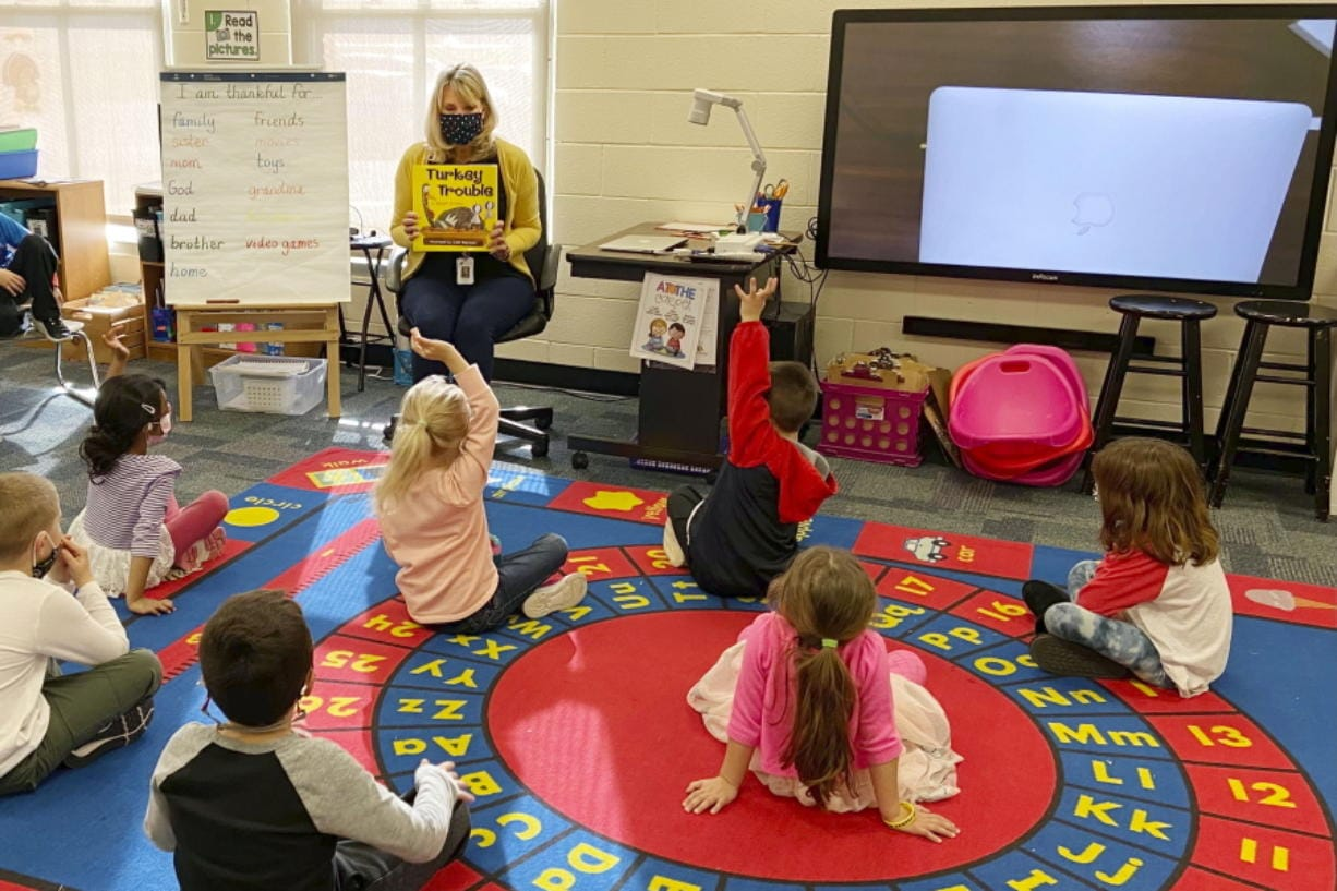 """In this photo provided by Julie Mackett, the kindergarten teacher conducts her class at Ft. Meigs Elementary School, in Perrysburg, Ohio. Contact tracing and isolation protocols meant to contain the spread of the coronavirus are sidelining school employees and frustrating efforts to continue in-person learning. """"I think everybody understands when you can't have enough subs to fill the roles, it's also a safety issue: You can't have that many children without support from adults,"""" said Mackett, who went through her own two-week quarantine early in the school year after a student tested positive."""