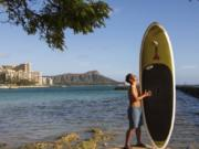 In this photo provided by Yoko Liriano, Bryant de Venecia poses for a photo with his paddleboard in Honolulu, Wednesday, Nov. 11, 2020. He started stand-up paddle-boarding when there were fewer tourists coming to Hawaii during the pandemic. He's among the Hawaii residents feeling ambivalence toward tourists returning now that the state is allowing incoming travelers to bypass a 14-day quarantine with a negative COVID-19 test.