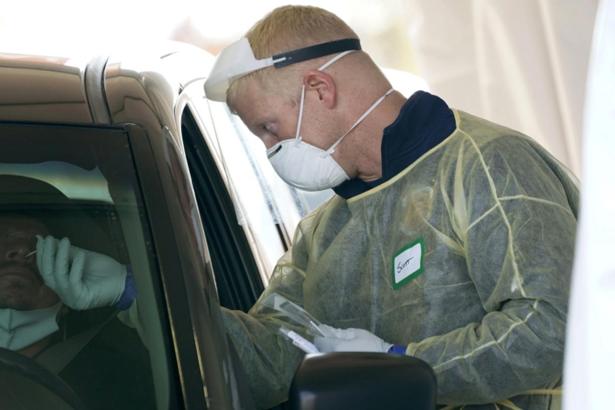 FILE - In this Oct. 28, 2020, file photo, a worker wearing gloves, a face shield, a mask, and other PPE administers a COVID-19 test at a King County coronavirus testing site in Auburn, Wash., south of Seattle. The latest surge in U.S. coronavirus cases appears to be larger and more widespread than the two previous ones, and it is all but certain to get worse. But experts say there are also reasons to think the nation is better able to deal with the virus than before, with the availability of better treatments, wider testing and perhaps greater political will. (AP Photo/Ted S.