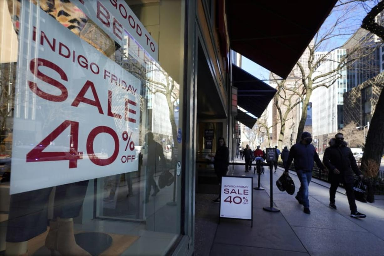 Shoppers pass an Indigo Friday 40% Off sign Saturday, Nov. 28, 2020, on Chicago's famed Magnificent Mile shopping district.