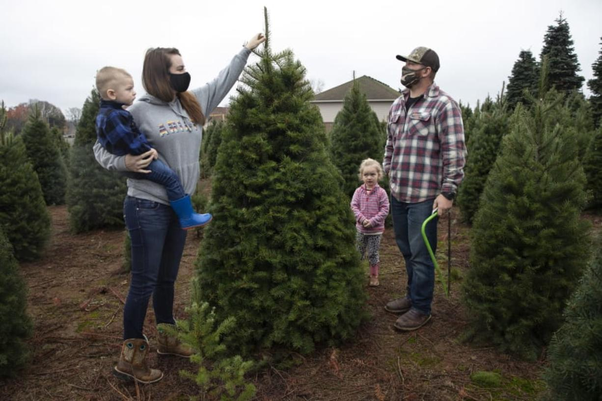 Josh and Jessica Ferrara shop for Christmas trees with son Jayce, 1 year and Jade, 3 years, at Sunnyview Christmas Tree farm on Saturday, Nov.  21, 2020 in Salem, Ore. It's early in the season, but both wholesale tree farmers and small cut-your-own lots are reporting strong demand, with many opening well before Thanksgiving.