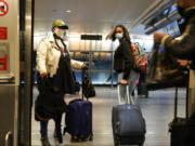 Travelers leave the AirTrain at JKF International Airport Friday, Nov. 20, 2020, in New York. Rising U.S. coronavirus cases, a new round of state lockdowns and public health guidance discouraging trips are dampening enthusiasm for what is usually the biggest travel period of the year.