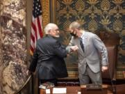 FILE - In this Nov. 12, 2020 file photo, outgoing Senate President Senate President Jeremy Miller, R-Winona gave Sen. David Tomassoni, DFL-Chisholm a congratulatory elbow bump before Tomassoni addressed the Senate Chamber. At least 187 state legislators nationwide have tested positive for the virus and four have died since the pandemic began, according to figures compiled by The Associated Press. Twelve Arkansas lawmakers have tested positive for the virus over the past month, the second largest known outbreak in a state legislature.