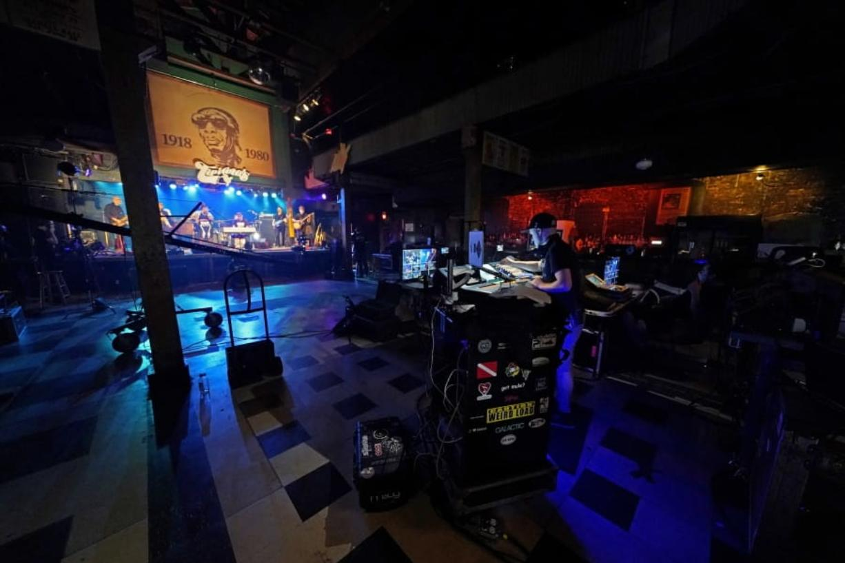 In this Oct. 26, 2020, photo, production engineers record the band Galactic for a video stream concert, inside an empty Tipitina's music club, which the band owns, in New Orleans. Music clubs all over the nation -- pop culture icons like the Troubadour in West Hollywood, the Bluebird Cafe in Nashville, The Bitter End in New York's Greenwich Village -- are shuttered due to the coronavirus. And owners fear for the future of their businesses and of a musical way of life.