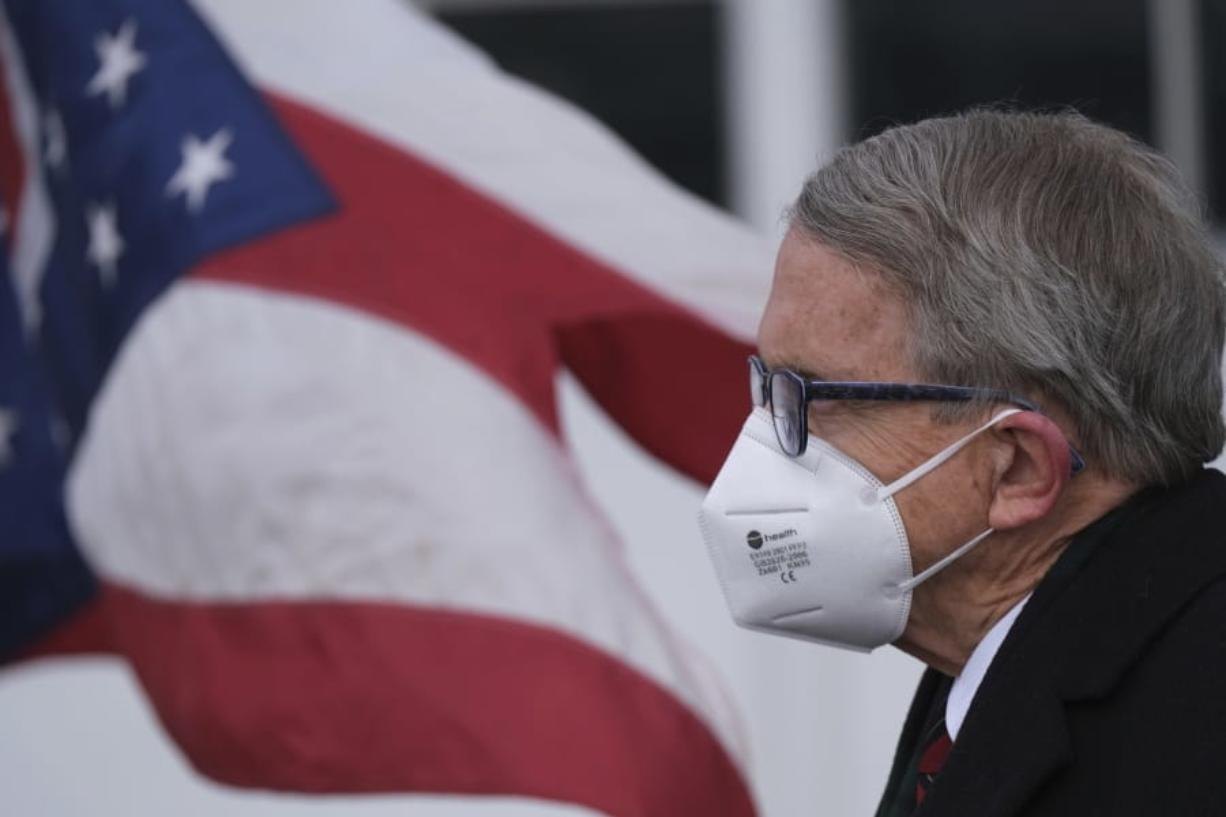 Ohio Gov. Mike DeWine looks on during a press conference Wednesday, Nov. 18, at Toledo Express Airport in Swanton, Ohio. On Tuesday DeWine announced a three-week 10 p.m. to 5 a.m. general curfew, with multiple exceptions, meant to slow the spread of the coronavirus as cases stay at near-record high levels. (J.D.