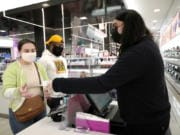 Cashier Druhan Parker, right, works behind a plexiglass shield Thursday, Nov. 19, 2020, as he checks out shoppers Cassie Howard, left, and Paris Black at an in Chicago. The accelerating surge of coronavirus cases across the U.S. is causing an existential crisis for America's retailers and spooking their customers just as the critically important holiday shopping season nears.