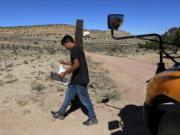 A student carries a math book delivered by school bus driver Kelly Maestas along his rural route outside Cuba, N.M., Oct. 19, 2020. The switch to remote learning in rural New Mexico has left some students profoundly isolated -- cut off from others and the grid by sheer distance. The school system is sending school buses to students' far-flung homes to bring them assignments, meals and a little human contact.
