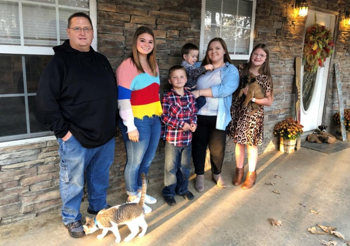 Keith Michael, left, poses with his children, from left, Jessica, Hunter, Houston, Sara and Holly, outside their home on Friday, Nov. 13, 2020, in Jonesboro, Ark. Among the victims of the coronavirus is Michael's wife, fourth-grade Arkansas teacher Susanne Michael, who died less than three months after celebrating the adoption of three of the children.