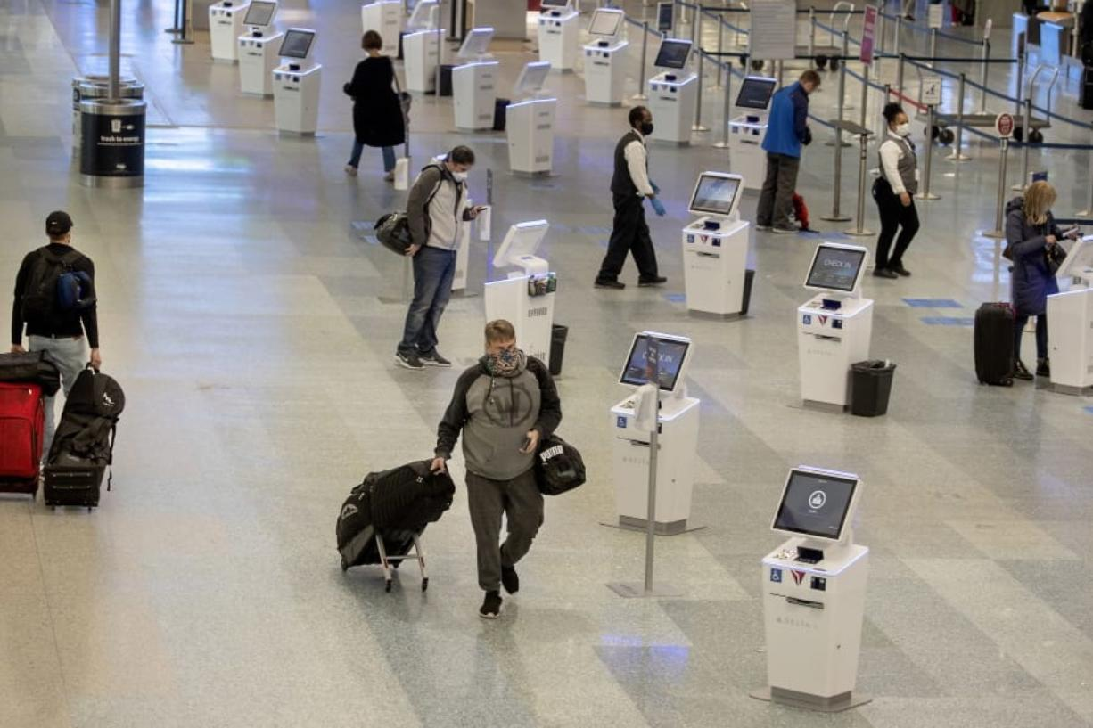 FILE - In this Nov. 12, 2020, file photo, travelers make their way through the Minneapolis-St. Paul International Airport during the coronavirus pandemic. With the coronavirus surging out of control, the nation's top public health agency advised Americans on Thursday, Nov.