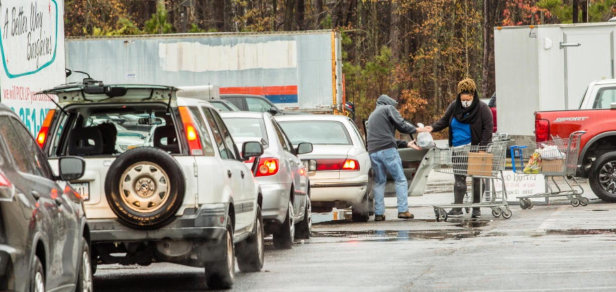 Volunteers at the New City Church food pantry in Peachtree City distribute dry goods, fresh vegetables and frozen meats to waiting cars outside the food pantry on December 16, 2020.