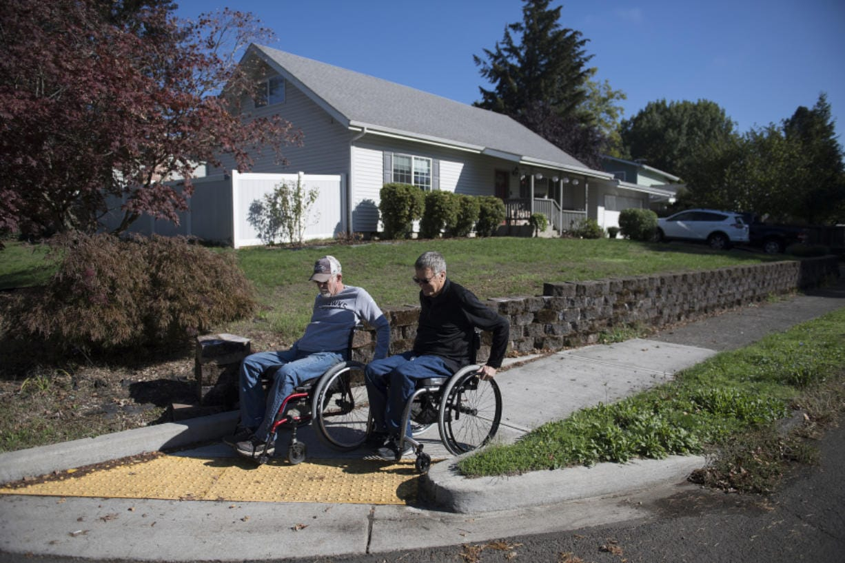 Vancouver resident Chuck Frayer, left, and friend John Williams show how they use a modern curb cut designed to make sidewalks accessible to people with all kinds of disabilities.