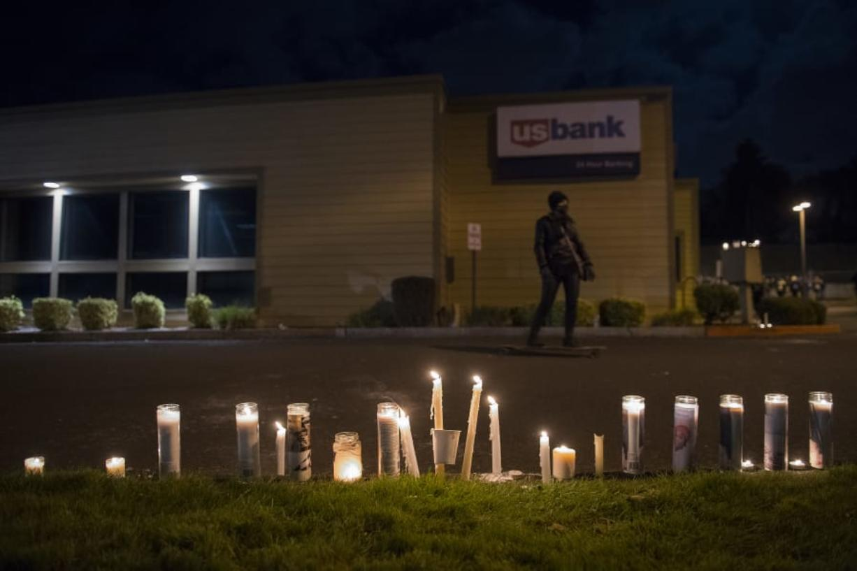 Candles in memory of Kevin Peterson Jr. are seen at the Hazel Dell branch of U.S. Bank on Oct. 30.