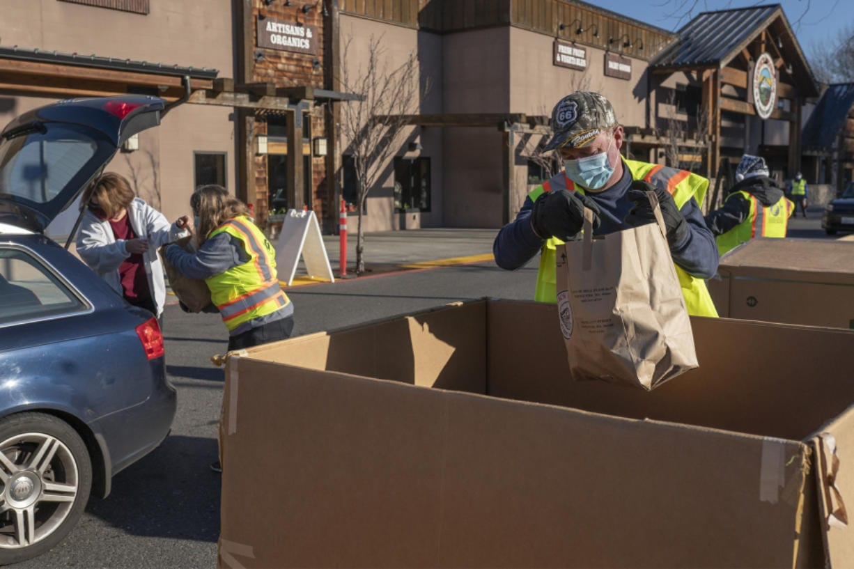 Volunteers unpack food donations from a car at the Salmon Creek Drive & Drop location Saturday morning. Volunteers manned eight locations throughout the county for the annual food drive.