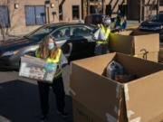 Volunteer Vicki Fitzsimmons, left, loads donations during a Drive & Drop food drive event in Salmon Creek. The annual Walk & Knock event was reorganized as a drive-thru due to the COVID-19 pandemic.