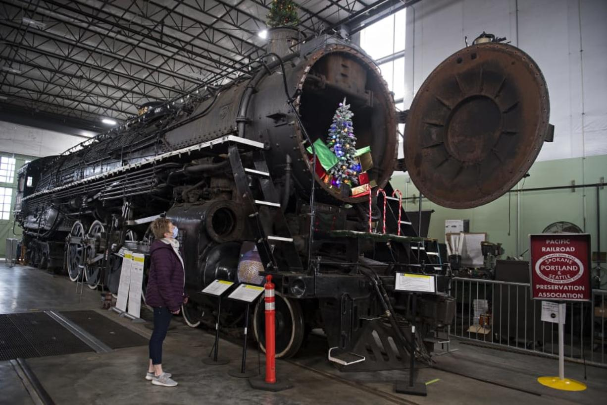 Renee Devereux of the Oregon Rail Heritage Center takes in the view of the SP&S 700, a steam locomotive that ran thousands of passenger trains through the Columbia River Gorge. It's been out of service since 2015 due to a federally required boiler inspection and maintenance. It may run again in 2021. At top, the SP&S 700 is equipped with eight drive wheels, each 77 inches in diameter.