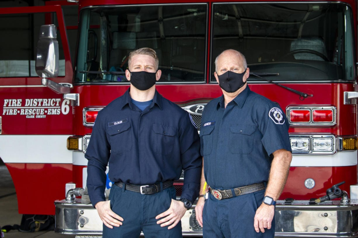 Firefighter and paramedic Max Olson, left, and firefighter and emergency medical technician Dave Fisher pose in front of a fire truck on Dec. 8 at Clark County Fire District 6 Station 61. They responded to the first reported COVID-19 case in the county.