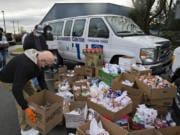 Walt Royle of Vancouver Heights United Methodist Church, left, joins fellow volunteers as they drop off Christmas gifts and supplies for workers Dec. 9 at sea at the Port of Vancouver administration building.