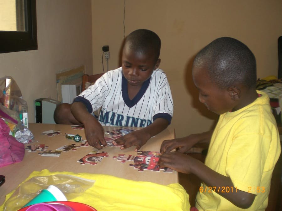 Jacques Badolato-Birdsell, left, and childhood friend Glody work on a puzzle in a hotel room in Kinshasa, Congo, before boarding a flight to the United States. Glowdy was adopted by an Iowa family.