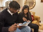 Jacques Badolato-Birdsell and his sister, Poonam Badolato-Niess, look at a photobook of Jacques' childhood at their Camas home. Badolato-Birdsell has signed with the University of Nevada to play football.