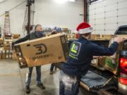 Rod Cook, left, helps load boxed-up bicycle kits into the back of a volunteer's pickup truck while Hayden Trent, right, repositions other boxes on Saturday morning at Taylor Transport in the Barberton area. Pre-registered volunteers drove though the warehouse to collect new bikes for home assembly. The bikes will be passed along to needy local families at Christmas.