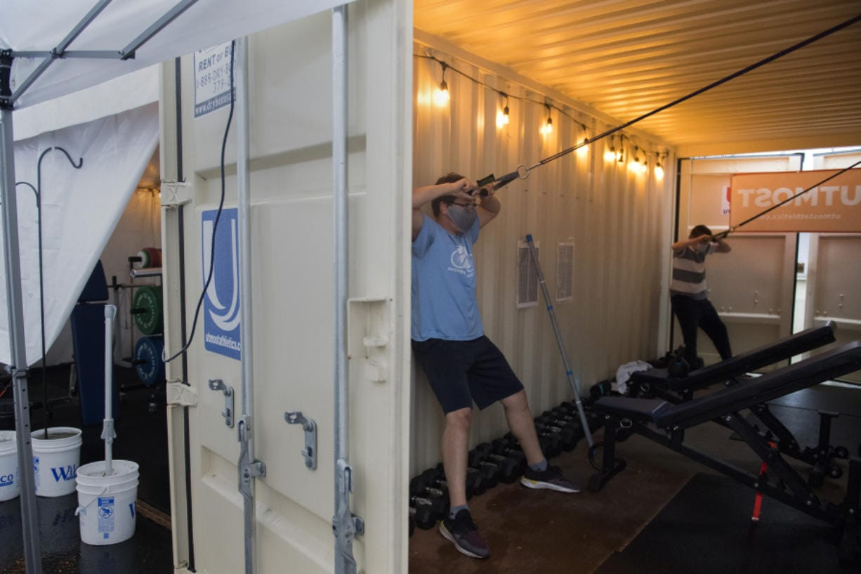 Zach Singleton, left, and Lucas Fabianek, both 16 and from Vancouver, get in a workout at Utmost Gym while using an oversize container for shelter outside Columbia Youth Center. Utmost Gym is just one part of The Columbia Future Forge, a nonprofit mentoring and training program to help young adults gain job skills and life skills.
