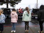 Learning Avenues students line up in front of Santa to sing Christmas carols with him for The Kids' Christmas, sponsored by workers at the Bonneville Power Administration. A pandemic-riddled 2020 made the event a socially distanced one this year.