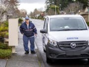 U.S. Postal Service mail carrier Cody Hershaw looks down the street as he gets back into his delivery car on a recent Thursday while on a route in the Cascade neighborhoods in Vancouver.