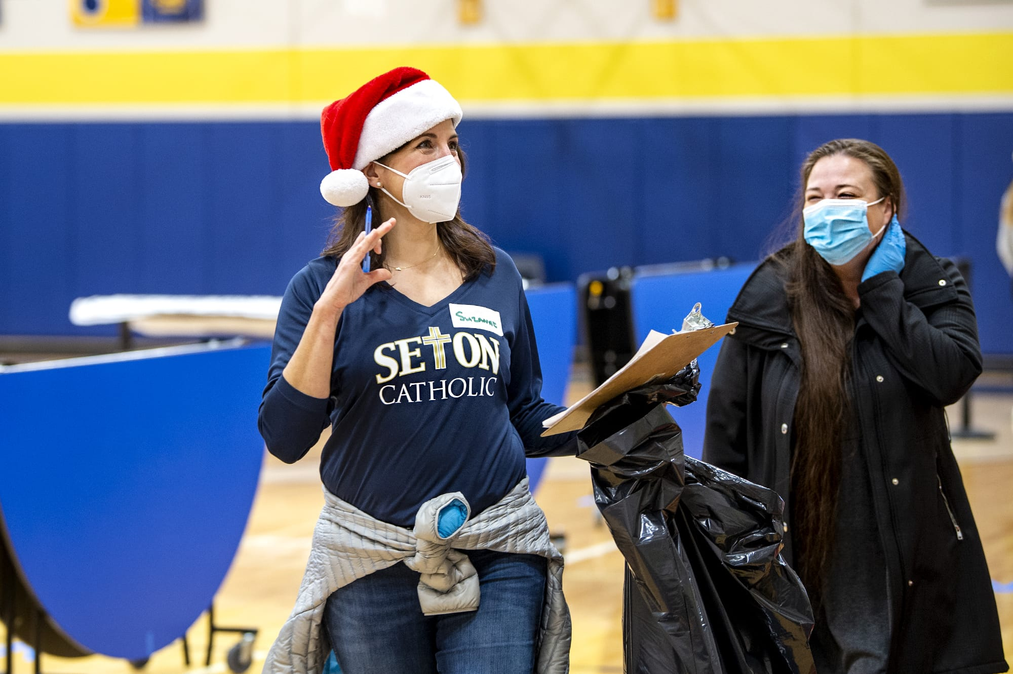 Parent volunteer Suzanne Gerhart, left, helps toy drive shopper Amy Buie on Saturday, December 19, 2020, at Seton Catholic Prep School. The toy drive was put on by St. Vincent De Paul, who used Seton Catholic's facilities and student and parent volunteers to serve the community. Guests were sheparded through the gymnasium and cafeteria to pick out toys, clothing, books, wrapping paper and enter raffles for a bike and a Christmas tree.