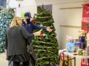 Seton Catholic principal Robert Rusk explains how the Christmas tree raffle works to a toy drive shopper on Saturday, Dec. 19, at Seton Catholic College Prep. Each guest could enter a ticket into one of the Christmas tree boxes. The winner will have the tree delivered.