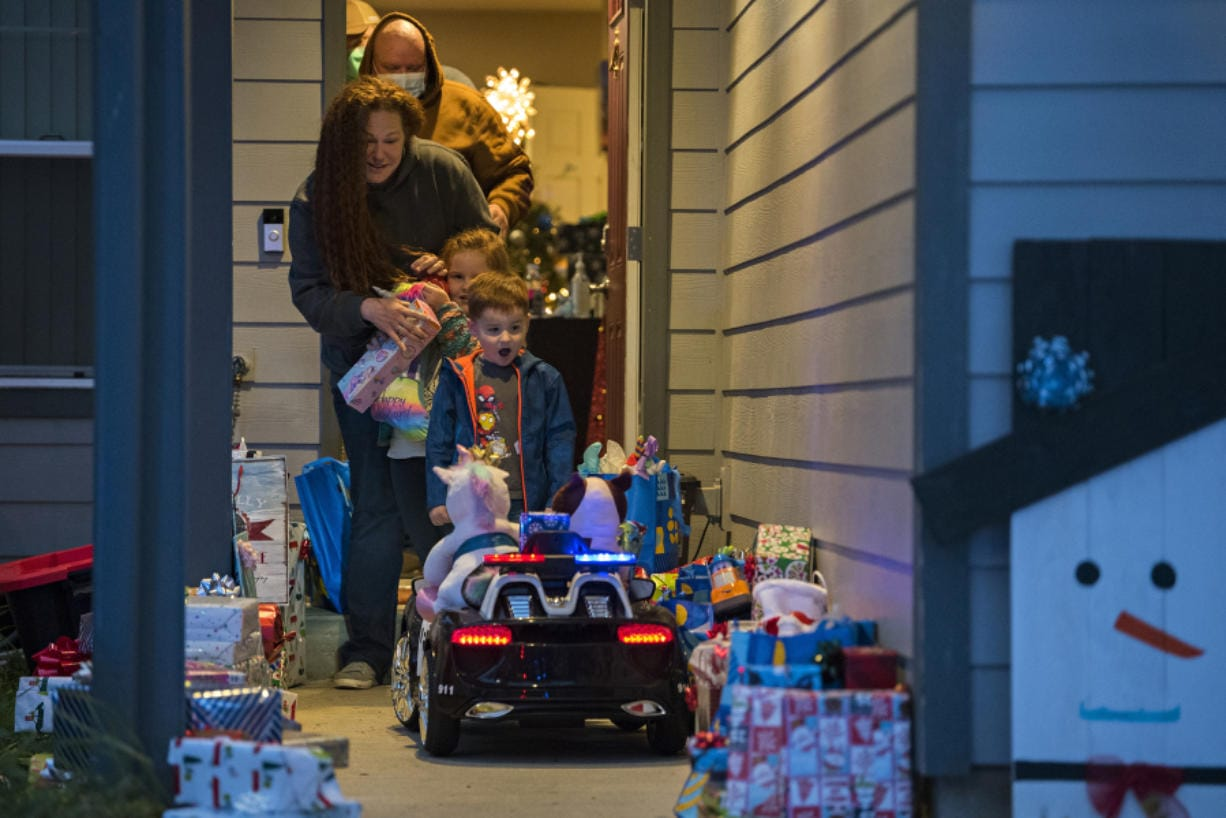 Kevin Hale, background in tan to front, of Longview joins his wife, Lindsay, his daughter, Annabelle, 6, and his son, Sawyer, 4, as they walk out to a porch full of donated gifts on Friday evening. Members of the Vancouver Police Department Domestic Violence Unit delivered the gifts to the family. Kevin Hale has been diagnosed with Stage 4 endocrine cancer, and his wife, Lindsay, works for the Clark County Prosecuting Attorney's Office as a victim advocate with the domestic violence unit.