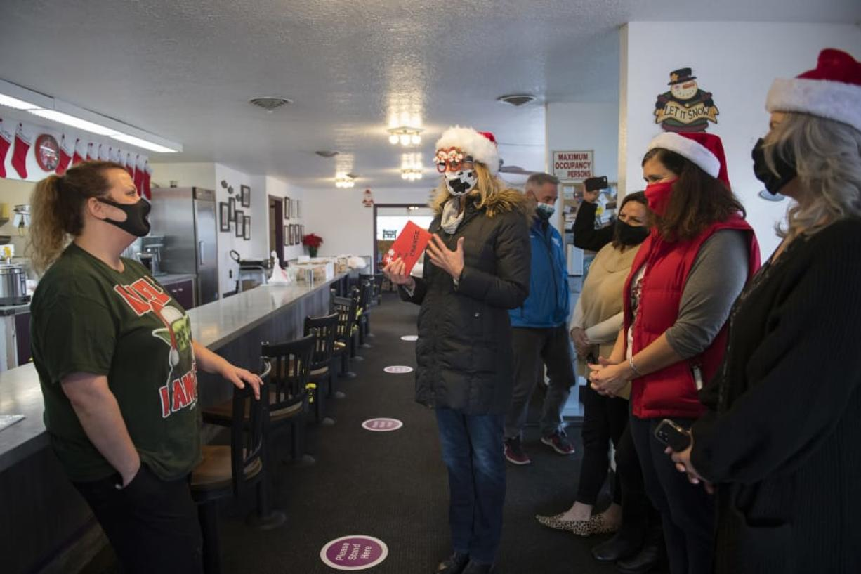 Shannon Holliday, manager at Carol's Corner Cafe, left, chats with Kathryn Tilkin of Hockinson, center, as the restaurant receives a generous holiday tip from Tilkin and her friends on Dec. 18. The group picked up a to-go order of 25 cinnamon rolls and left a holiday card with $3,100 to support the restaurant, which has been struggling due to COVID-19 restrictions.