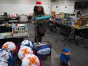Karen Morrison of Odyssey World International Education Services sorts through gifts for children in need at Bridgeview Resource Center in Vancouver.