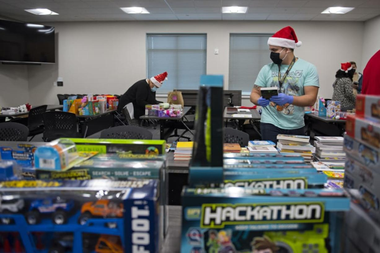Damien Wheeler of Bridgeview Resource Center in Vancouver joins fellow helpers as he sorts through Christmas gifts for kids. The toy drive served about 150 local families during a year when many have lost jobs due to the COVID-19 pandemic.