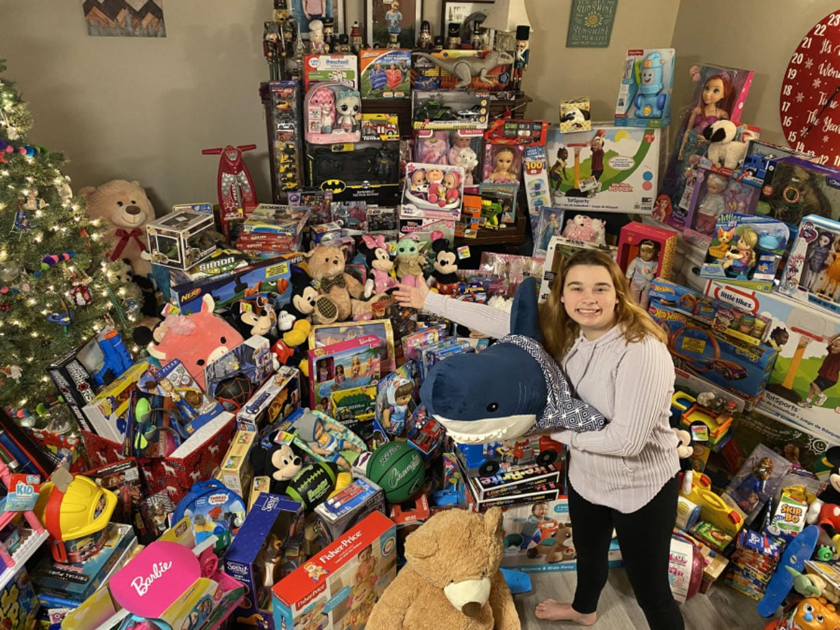 "Madeline McMillen poses with some of the 728 toys donated by friends, family and businesses. ""I want children to have good Christmases and make sure they're still loved,"" the Prairie High School sophomore said."