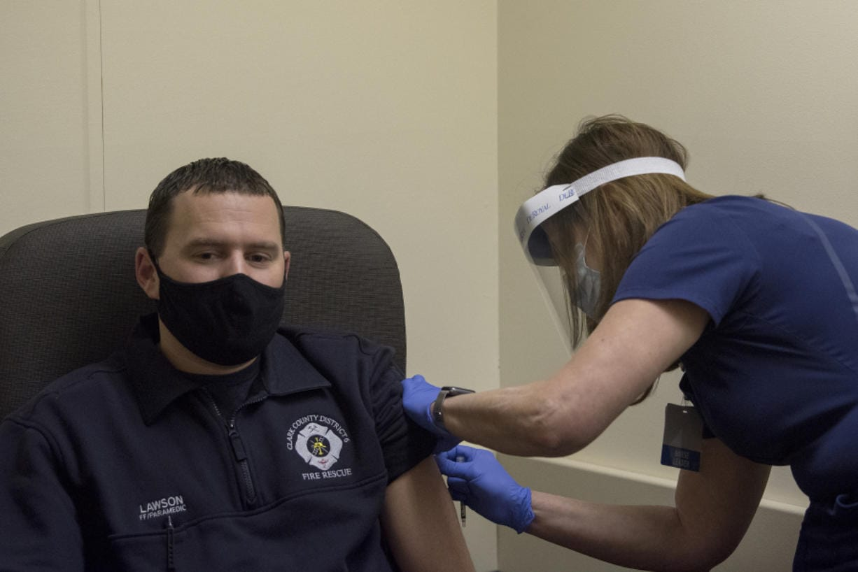 Firefighter and paramedic Josh Lawson, left, waits as system director Sara Williams applies a bandage after he received a COVID-19 vaccination at PeaceHealth Southwest Urgent Care in Vancouver. PeaceHealth has administered the vaccine to nearly 100 first responders from Clark and Cowlitz counties. The plan is to give roughly 200 first responders the first dose of the vaccine over the next couple weeks.