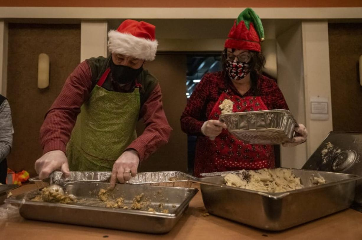 Steve Helland, left, and Marty Forsmann, both of Vancouver, load mashed potatoes and stuffing into to-go containers on Friday at a Christmas meal distribution event at WareHouse '23.